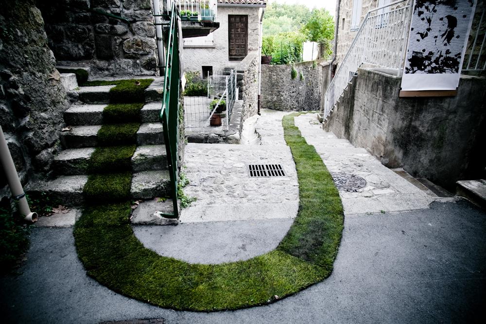 Gaëlle Villedary och det mossgraffitiverk hon skapade till staden Jaujac i sydöstra Frankrike. (Foto David Monjou)