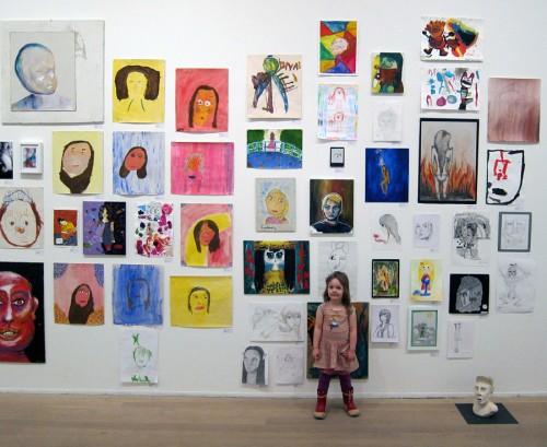 Vanna framför väggen med porträtt i Moderna Museets utställning Konstplaneten, av barn mellan 1-19 år. Hennes teckning är rakt ovanför hennes huvud näst längst upp. (Foto Anders Engström)