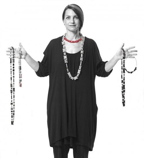 Katarina Briedits med sina halsband gjorda av tvättrådslappar från plagg på Myrorna. (Foto Norstedts/Stockholms Auktionsverk)