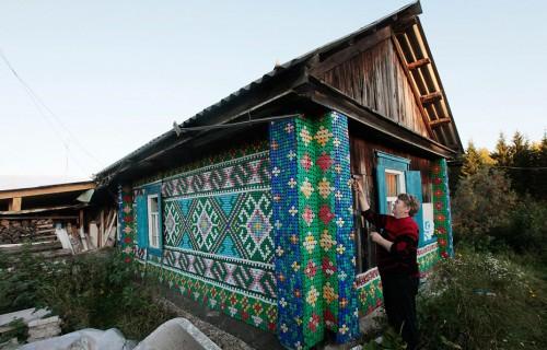 Olga Kostina i ryska byn Kamarchaga spikar på sitt hus. 30 000 kapsyler bildar traditionella mönster. (Foto: © REUTERS / Ilya Naymushin)