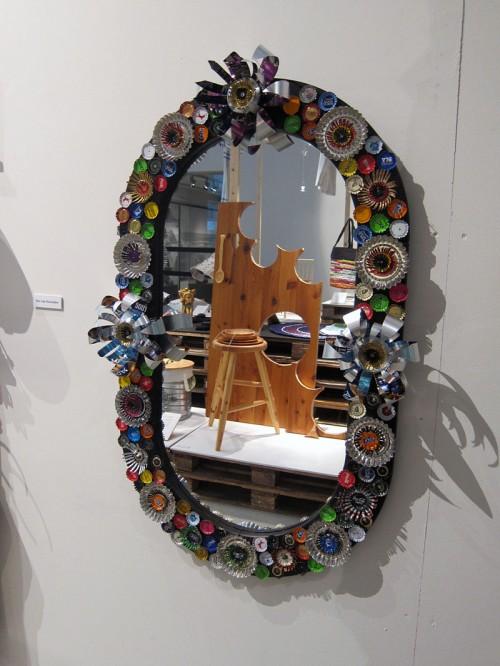 Välsmyckad spegel - kapsyler och plåt. I spegeln skymtas också vad som går att göra av en gammal avlagd bordsskiva. Hans Bergendahl ligger bakom spegeln och Bengt Bäversten har gjort pallen och skålar. (Foto Kurbits)
