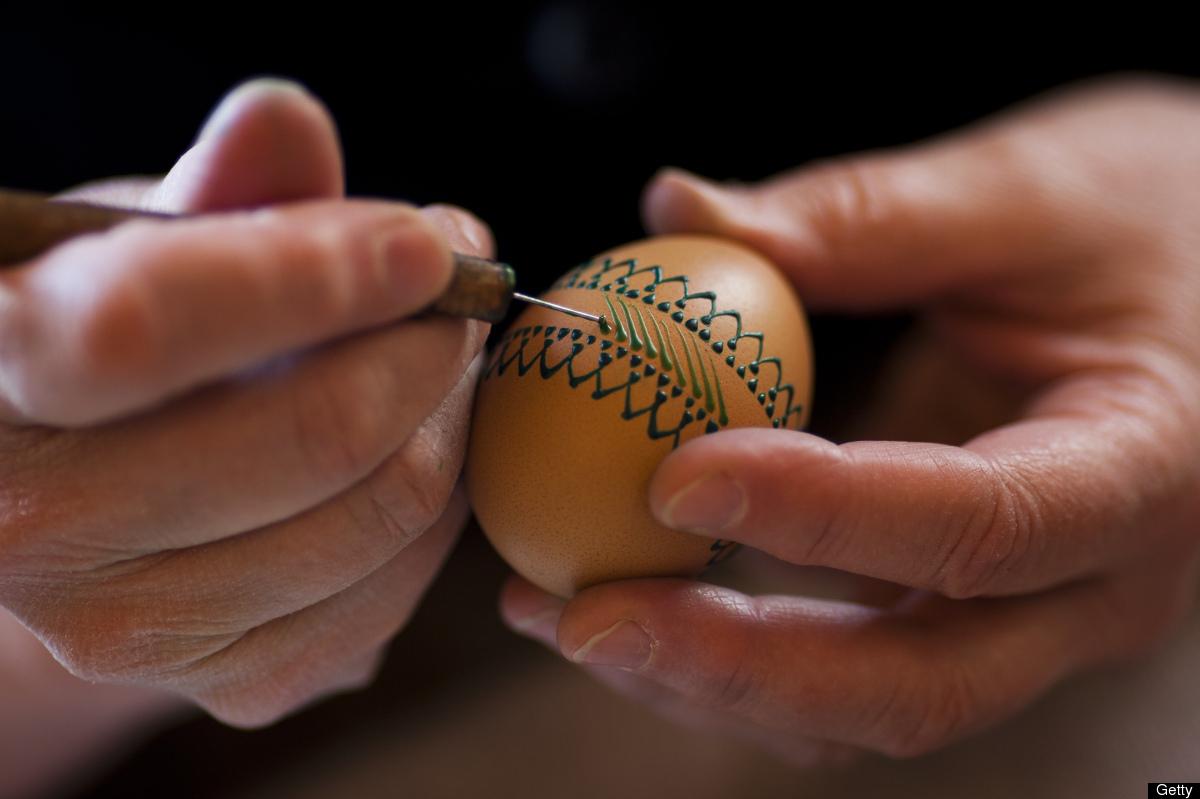 Skickliga händer dekorerar ägg. (Foto Huffington Post)
