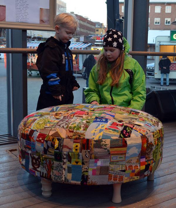 Pall med tema glädje, gjord av åttio slöjdelever i årskurs tre och fyra på ett par av Umeås skolor. Här är den färdiga pallen utställd och beundras, kanske av ett par görare? (Foto Stina Westerlund)