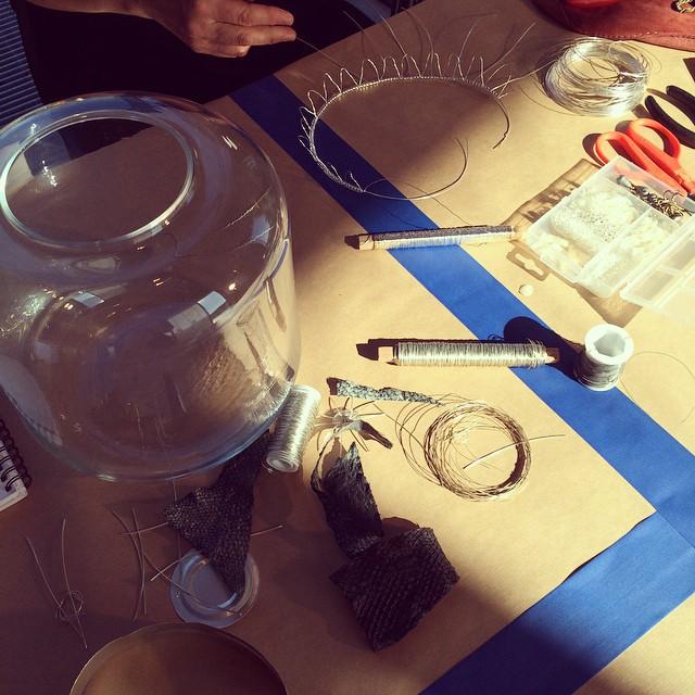 Anette Nilssons material är tråden, här är hon i full gång att göra en krona till vasen. Metalltråden varvas med pärlor och fiskfjäll (!) som gav ett fint skimmer. Anette ville behålla vasens funktion men addera utsmyckningen. Materialet är matchat till att passa vatten.  (Foto Kurbits)
