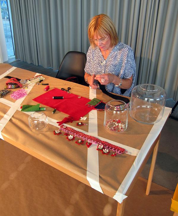 Anna Wengdin med applikationer, broderi och pärlor förvandlade vasen till ett smyckeskrin, där halsband och armband samsas. Dekorationen som hon förberett blev alltså för kort, vilket hon satte igång med att lösa. (Foto Kuribts)