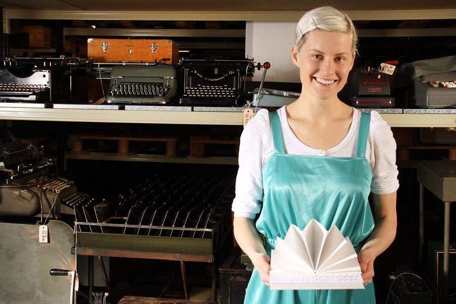 Ida Gerdemark med en av sina serieförvaringsböcker med inspiration från ett registerbord och ett kopparstick. (Foto Sörmlands museum)