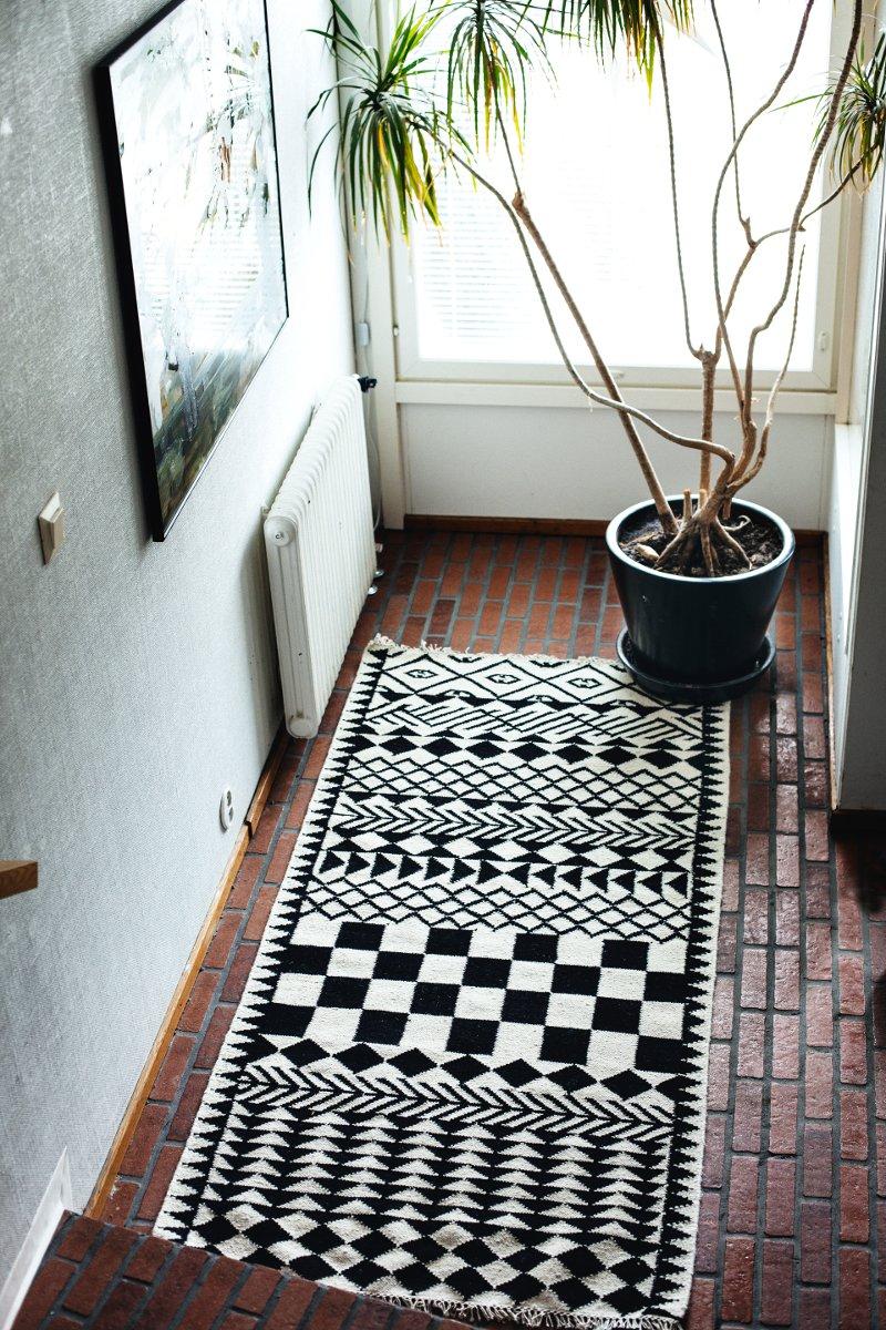 Mum's började som ett konstprojekt i Afrika 2006, då Outi såg möjligheten att kombinera traditionell afrikansk mönsterskatt och hantverk med skandinavisk design. Här är mattan Kassena original black.  (Foto Suvi Kesäläinen / Mum's)