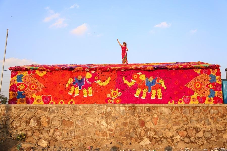 För kvinnors rättigheter och allas lika värde hälsar Olek från taket i den nyligen avslutade installationen i New Dehli. Övernattningshemmet Raine Basera för hemlösa kvinnor i New Dehli har fått en garnkostym. (Foto © Pranav Mehta/St+ARTDehli)