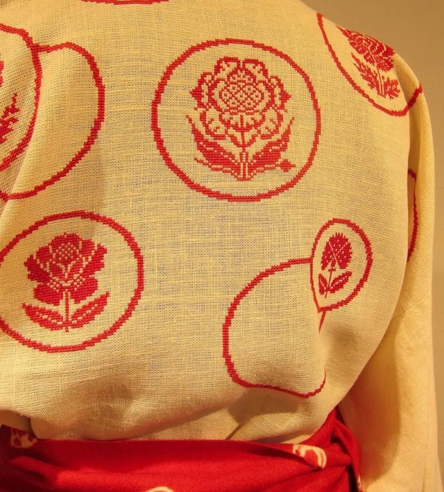 Detalj av en av Eva Davidssons dräkter, där kimonoblusen är gjord i hampa med broderier på. Resten av dräkten har kjol och skärp i shiboriteknik i ull, liksom muddarna som är gjorda iktatteknik och stickning. (Foto Kurbits)