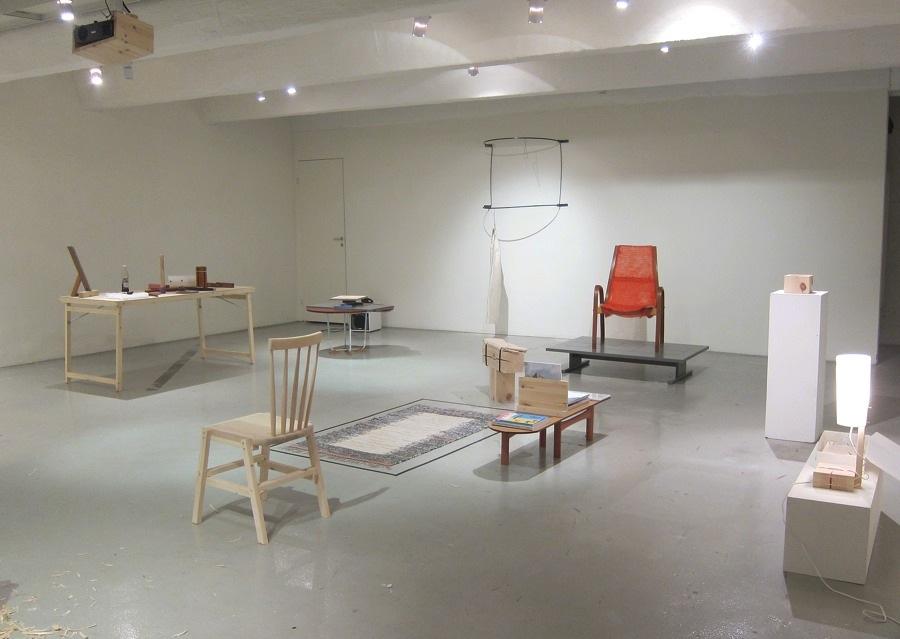 Den röda stolsryggen gjord av en nätsäck för gissningsvis lök eller apelsiner i bakgrunden,  liksom andra pågående möbler och projekt i utställningen Make Up av Thomas Lissert. (Foto Kurbits)