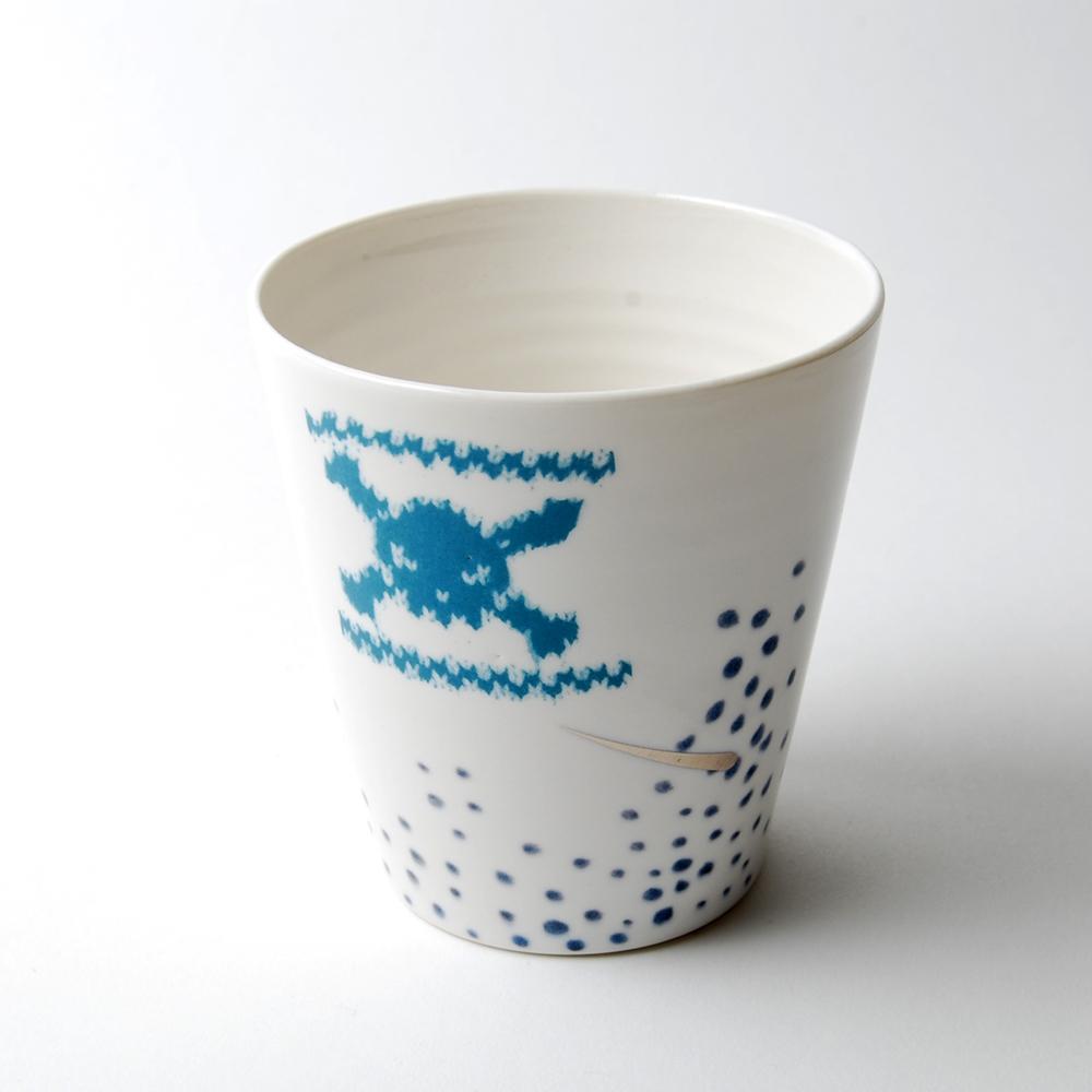 Det här är ett nytt samarbete mellan textilkonstnären och stickaren Anna Bauer som står för de fina hönsestrikkmönstren och keramikern Eva Zethraeus, som står för själva muggen. (Foto Konsthantverkscentrum)