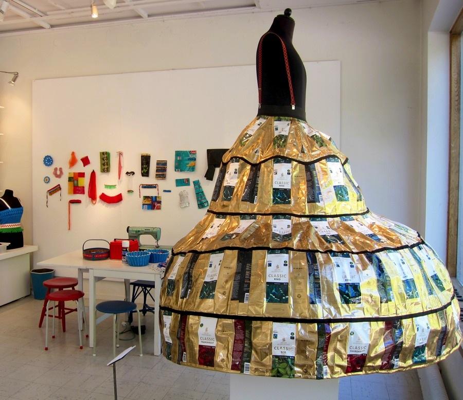 Den dramatiska kaffepaketsklänningen i blickfånget i galleriets entré - sett bakom den workshophörna där Johanna samlat delar av sitt material. (Foto Kurbits)