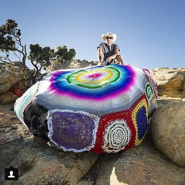 Stephen Duneier på en av de stenar som han tillsammans med världens garncommunity lät klä in med garn. (Foto Stephen Duneier)