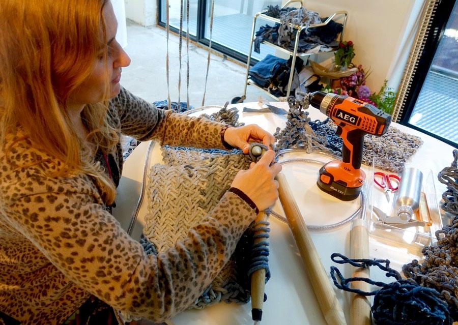 Agnes Nissen samlar avlagda jeans och återanvänder trasorna som hon spinner ihop till snoddade remsor, likt garnnystan, med hjälp av en skruvdragare. Här stickar hon en matta med egengjorda sticko.r (Foto Kurbits)