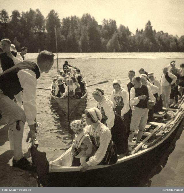 Kyrkbåtar i Leksand vid midsommar. Män, kvinnor och barn klädda i folkdräkter från Dalarna. Fotot är taget 1941 och i fotografuppgifterna står Kristoffersson, Hr. (Källa digitaltmuseum.se)