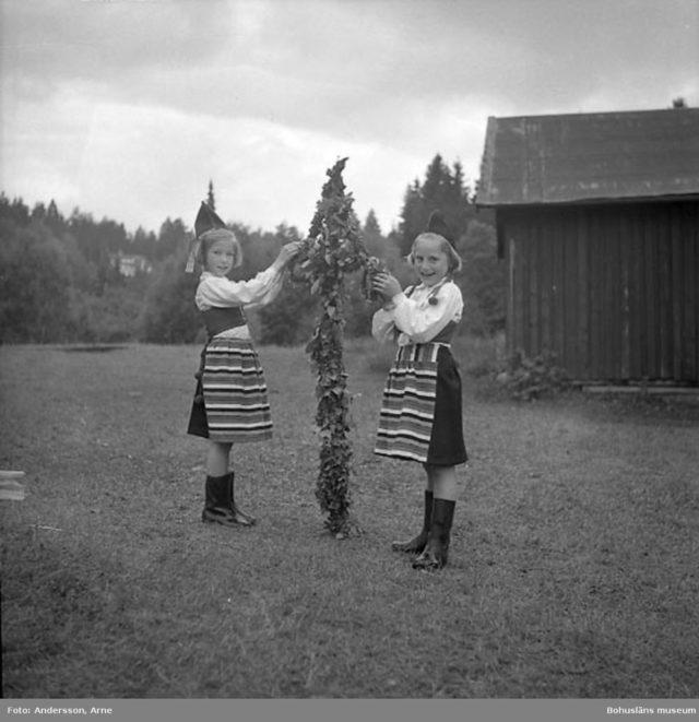 """""""Midsommarfest Juni 26/6"""" enligt fotografens notering.Flickorna bär plagg inspirerade av rättviksdräken och till det gummistövlar. Troligen en blöt midsommar! - ur museets anteckningar. Bilden är tagen 1948 av Arne Andersson (liksom bilden in inläggets topp) (Källa digitaltmuseum.se)"""