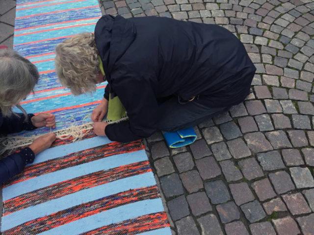 Monica Modig Rauden, här till höger i bild, tillsammans med medhjälpare imorse nästandes ihop mattan. (Foto Carina Olsson)