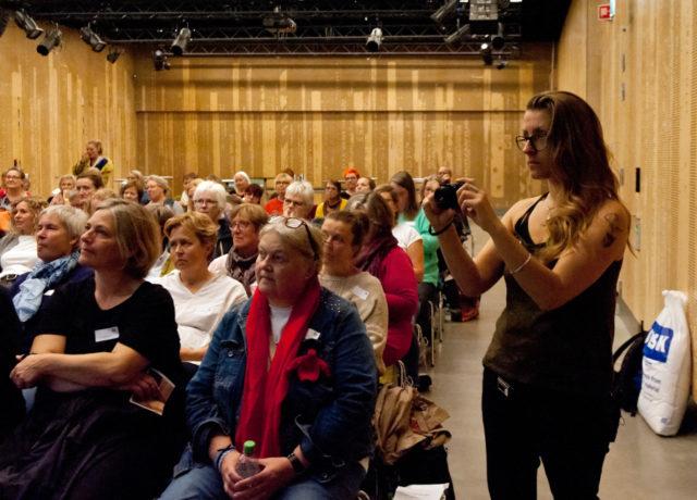 En finfin publik! Här i mitten med röd halsduk sitter Agnete Rasmussen, ordförande i Gavstrik och initiativtagare till dagen. Fotandes till höger i bild Eva mm Engelhardt som höll i en av de spännande workshoparna under eftermiddagen. (Foto Jørgen Diswal, FoF Aarhus)