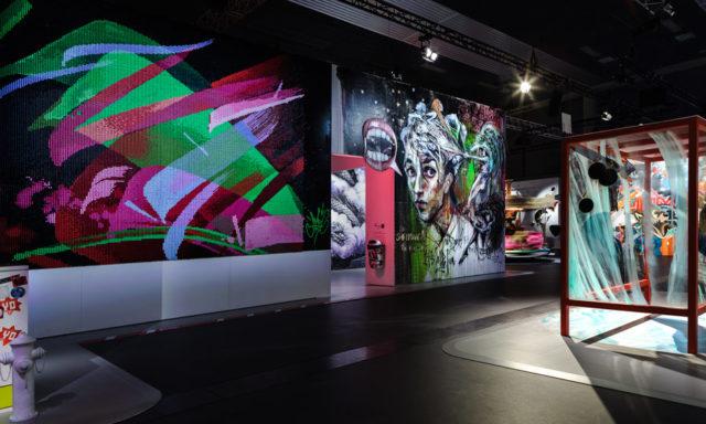MadC, konstnär från Tyskland närmast i bild. Hon har här använt 45 000 sprejburksmunstycken som målats i 43 färger. Det tog nio personer sex veckor att färdigställa dem, lär jag mig i den mycket informativa katalogen som också är framtagen till utställningen. (Foto Rainer Kurzeder)