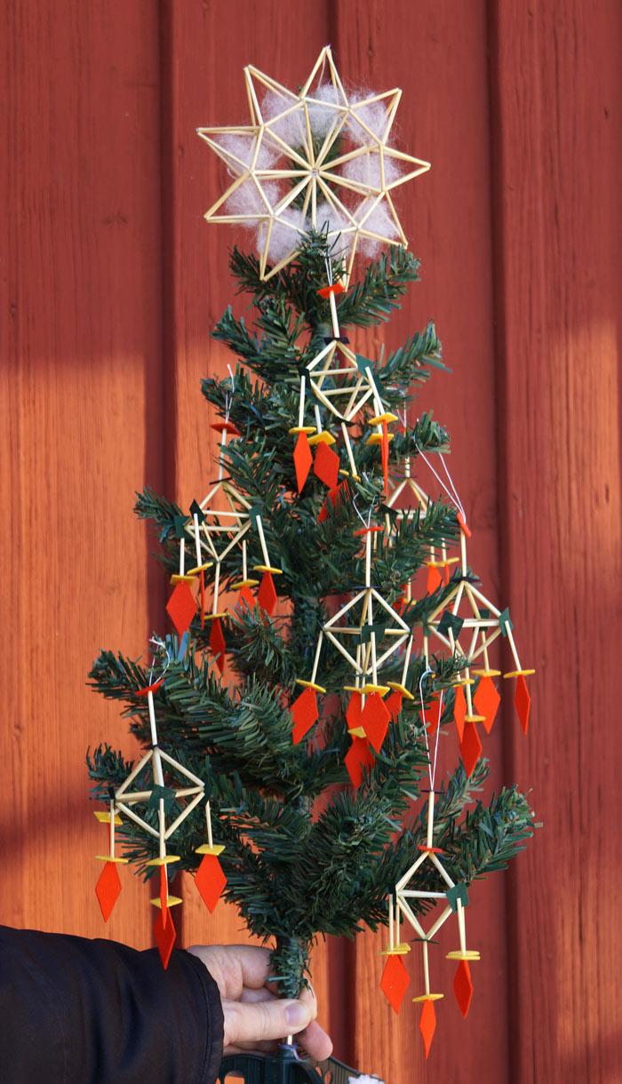 """Miniatyrgran. Dekorerad med """"flugguskepp"""" - det vill säga råghalm och dräktkläde från Leksandsdräkten. Toppstjärnan är gjord i råghalm och kardflor. Allt av Per-Åke Backman. (Foto Ingela Sannesjö)"""