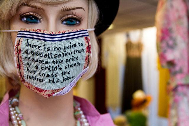 En broderad protest för att få oss att tänka till vad gäller produktionsvillkor för de produkter vi köper. Masken sitter på en skyltdocka i ett fönster i Shoreditch, London. (Foto Robin Prime/Craftivist Collective)