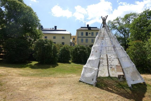 Lavvu kallar samerna denna tältkonstruktion och det är också namnet på kvinnonätverket Hemmas arbete som står hela sommaren i slottsparken i Löfstad utanför Norrköping. All textil är återbrukad och ihopsatt av kvinnorna som ett sätt att uppvärdera och ta tillvara tidigare generationers arbete. (Foto Kurbits)