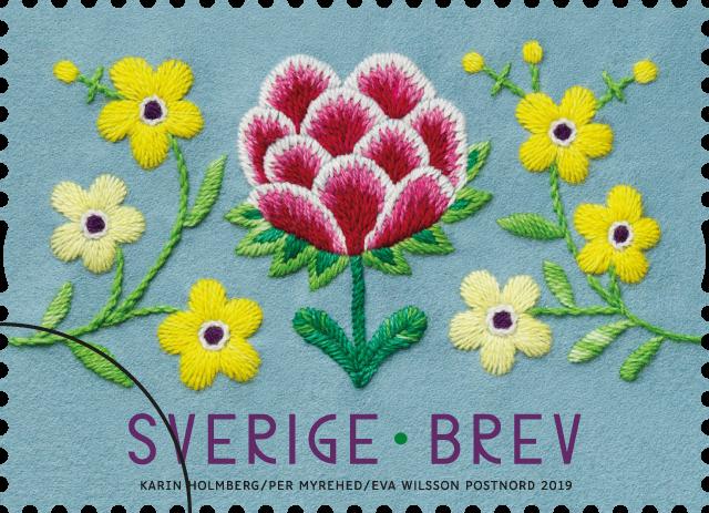 Karin Holmbergs broderi pryder inrikesportot och är lagt till rullen, då hennes blombård löper från frimärke till frimärke så som den traditionella bården fungerar. (Foto Postnord/Per Myrheden)