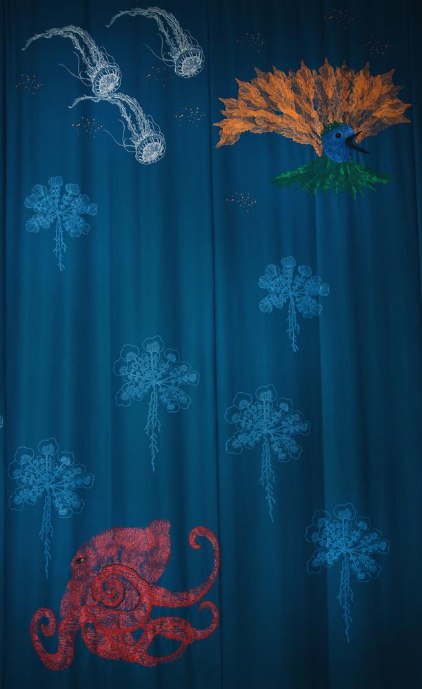 """""""Världen befolkas av de mest underliga och fantastiska varelser, som t.ex den lilla kolibrin med fyra stjärtfjädrar. Verklighetens fantasi och magi. Eller pelargonbladen, alldagliga visar de på det vackra i vardagen. Här tryckta i guld"""", säger Carina Marklund om sin ridå. (Foto Carina Marklund)"""