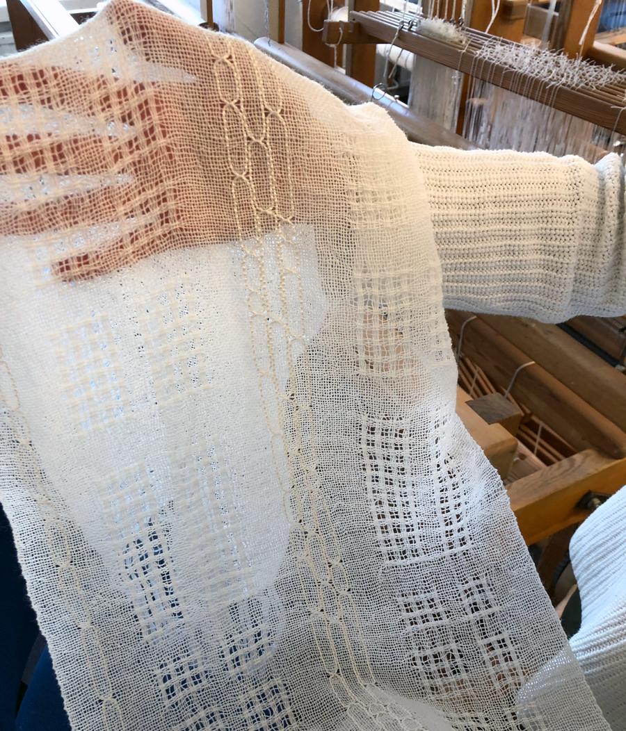 Den färdiga gardinen som Eva Mendel här visar för mig, i utställningen blev de monterade mot svart så kontrasten blir extra tydlig. Ett mycket vackert experimenterande. (foto Kurbits)